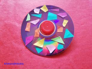 CD mit Papierschnipseln und Verschlusskappe beklebt