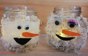 Leuchtende Schneemänner aus wei Marmeladegläsern mit Kunstschnee, Augen, Nase, Mund und Teelichtern im Inneren