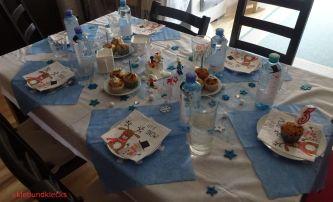 Tisch geschmückt mit Streuteilen, glitzernden Kugeln, blauen Servietten und Muffins