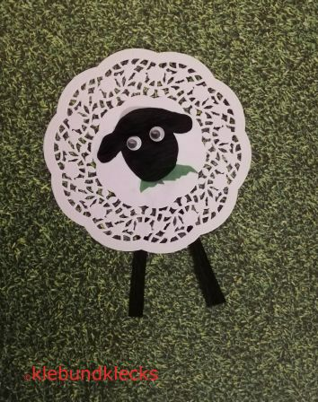 Schaf aus Tortenuntersetzern mit schwarzem Kopf, Wackelaugen und Gras im Maul