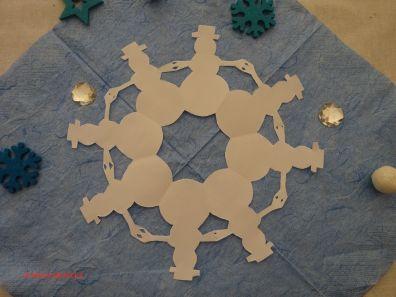 Schneemänner aus Papier halten sich im Kreis an den Händen