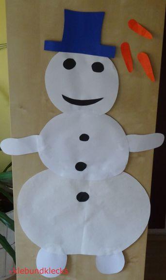 Schneemann aus Papier mit Karottennasen daneben zum Pinnen